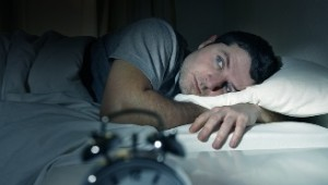 man in bed with eyes opened suffering insomnia and sleep disorder