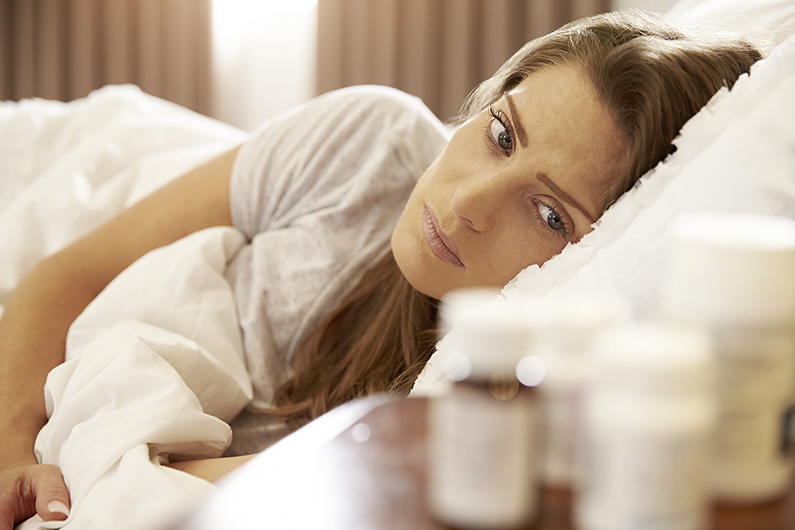 Unhappy Woman Looking At Medication On Bedside Table