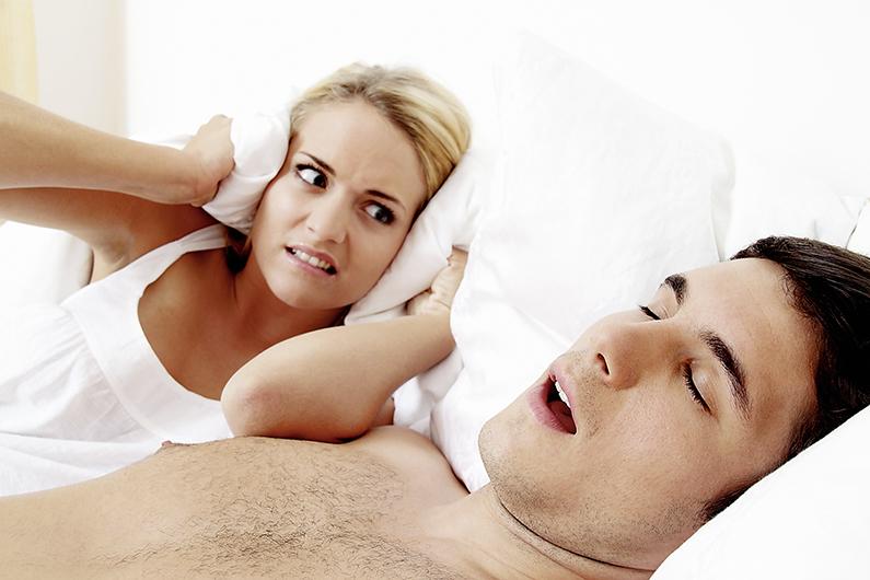 Paar im Scvhlafzimmer. Mann schnarcht laut und unangenehm.