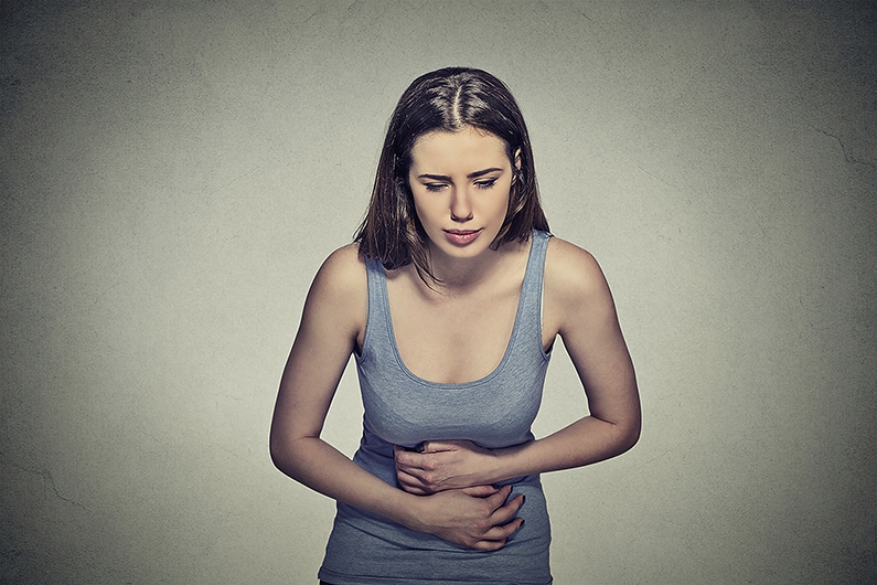Portrait young woman hands on stomach having bad aches pain isolated on gray wall background. Food poisoning, influenza, cramps. Negative emotion facial expression reaction health issues problems