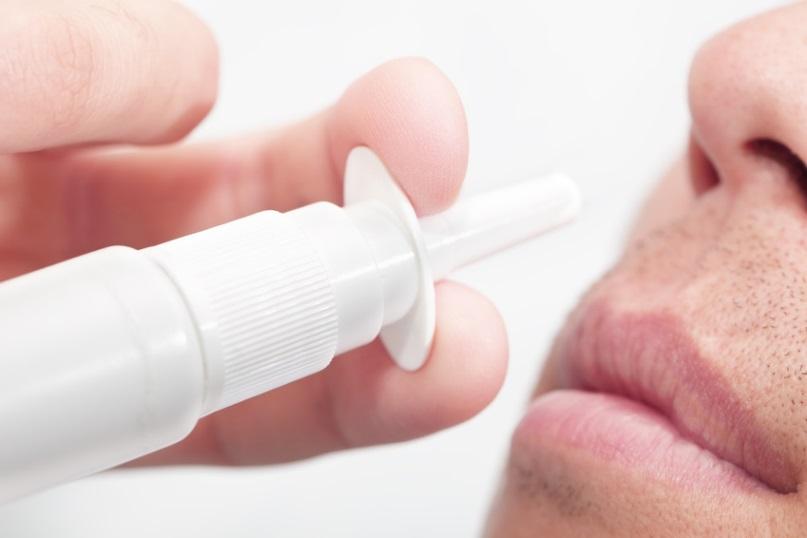 Man sprays medicine for allergy in nose