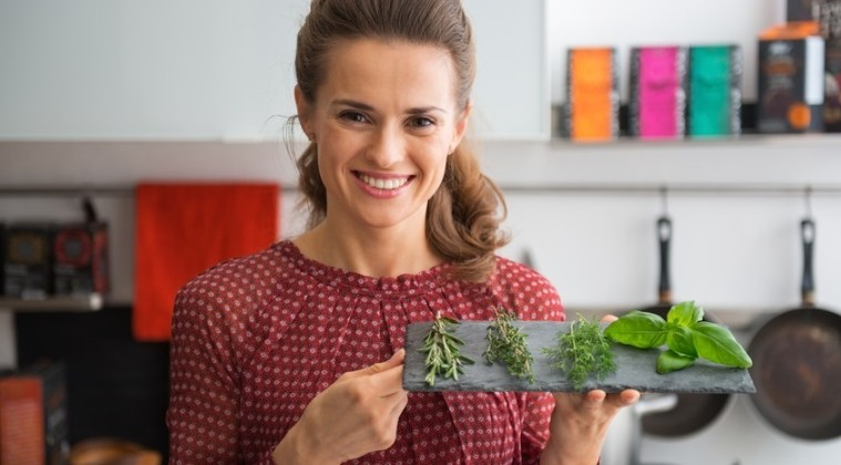Portrait of happy young housewife showing fresh spices herbs on stone substrate