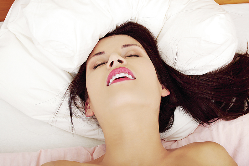 Young woman is lying in bed and having orgasm, in home.