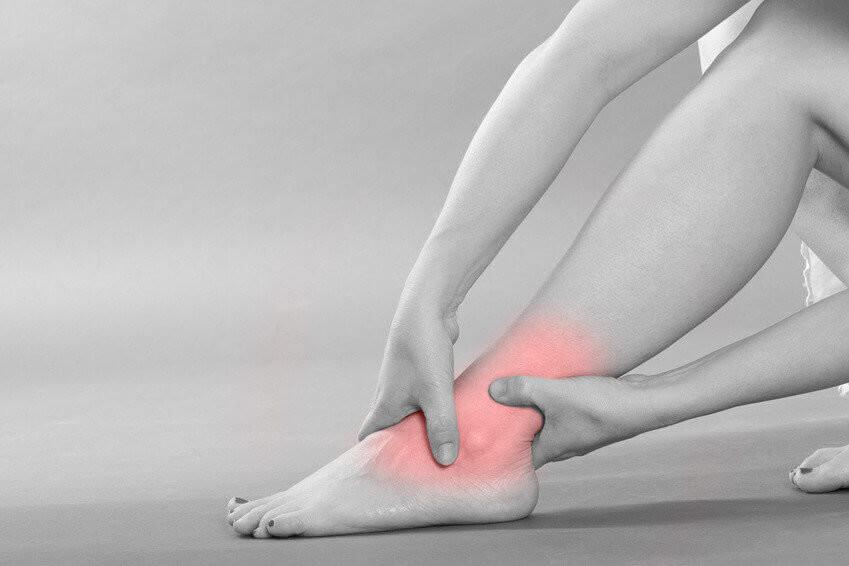 Sprunggelenk Schmerzen - schwarz wei mit rotem Schmerzpunkt
