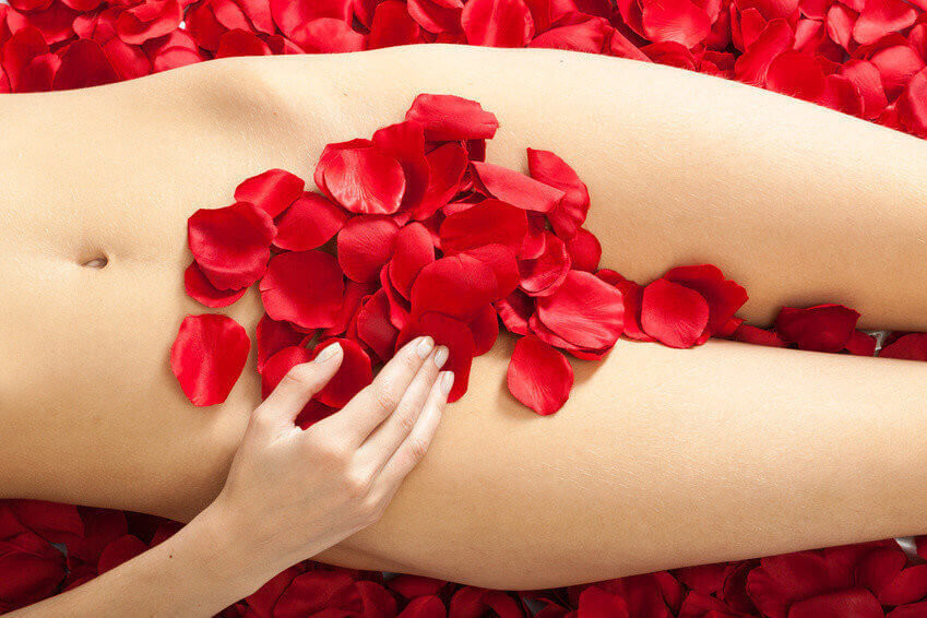 female body with red rose petals