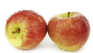 two whole braeburn apples on a white background