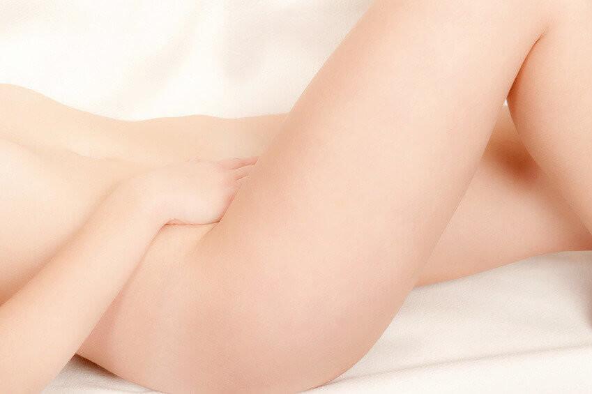 Klassische Nahaufnahme einer nackten Frau auf weißem Bett