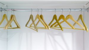 Yellow wooden hangers in a closet