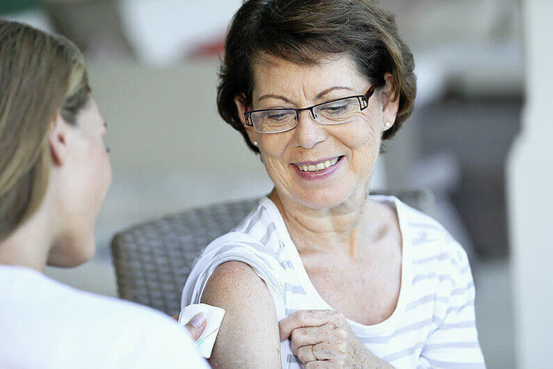 Senior woman receiving flu vaccine