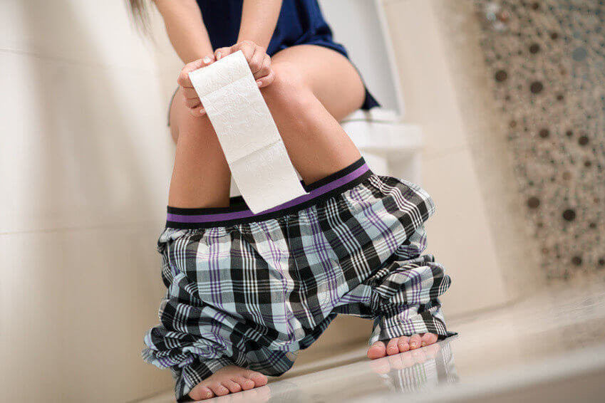 Woman with stomach problems on toilet