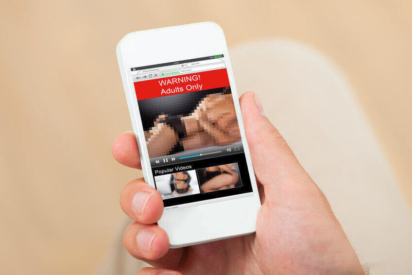 Close-up Of A Person Hand With Adult Movie On Mobile Phone