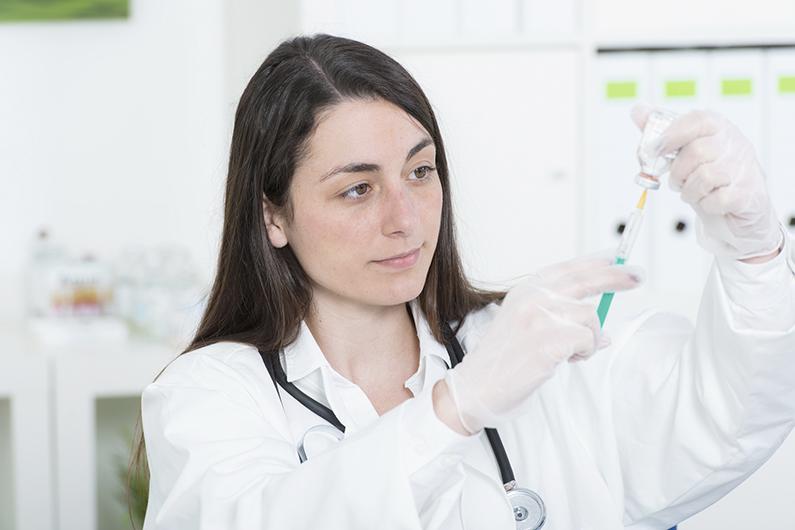 Junge rztin zieht Spritze mit Impfstoff auf