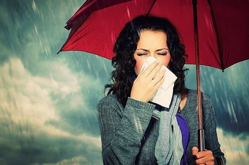 Sneezing Woman with Umbrella over Autumn Rain Background