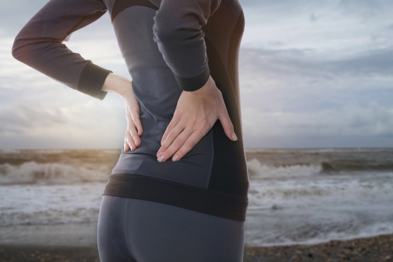 Back Pain. Athletic fitness woman rubbing the muscles of her lower back outdoors. Sports exercising injury.