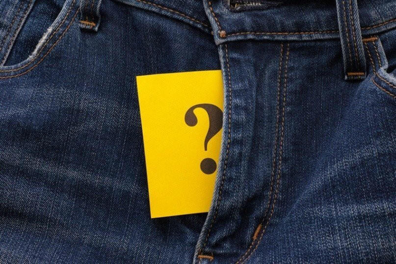 Yellow paper note with question mark appears out in jeans fly