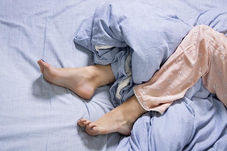 Weibliche Füße mit Schlafanzug im Bett am Morgen in blauer Bettwäsche