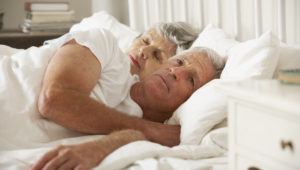 Senior Woman Tries To Be Affectionate Towards Husband In Bed