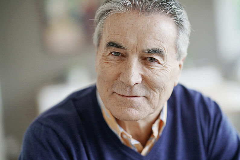 Portrait of senior man with blue sweater looking at camera