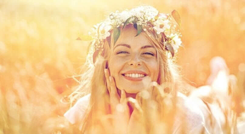 happy woman in wreath of flowers on cereal field