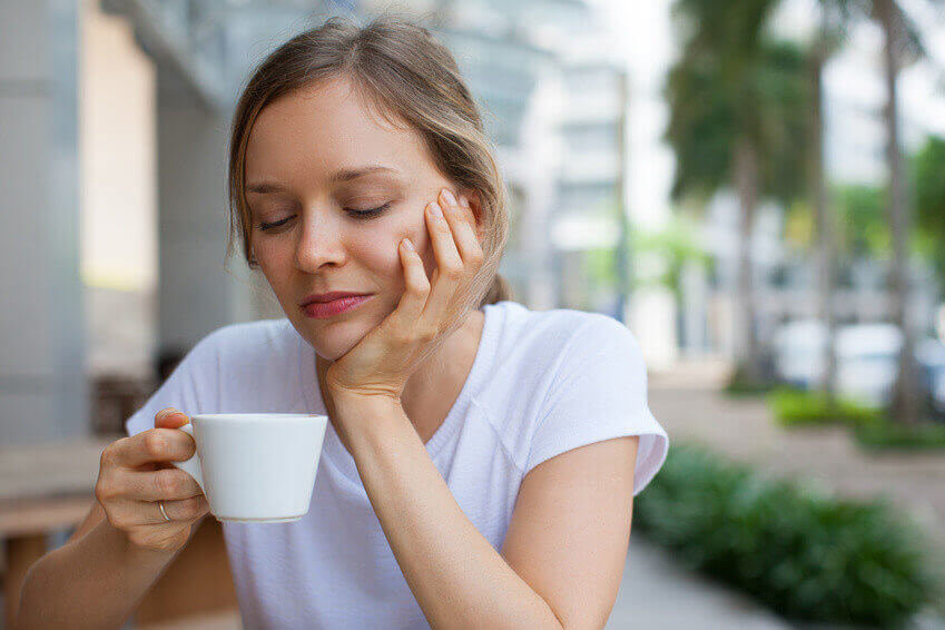 Closeup portrait of bored young beautiful woman leaning head on hand, drinking coffee outdoors with blurred street view in background. Front view.