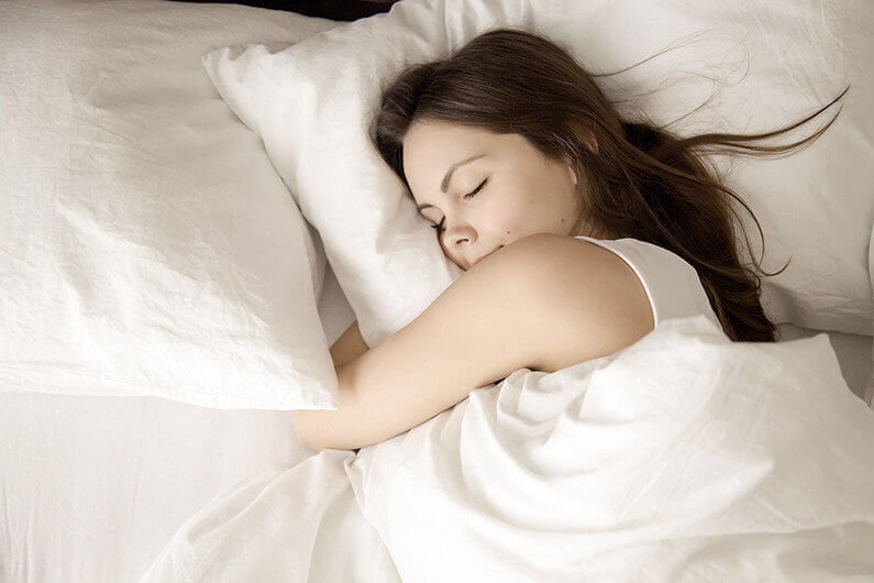 Top view of attractive young woman sleeping well in bed hugging soft white pillow. Teenage girl resting, good night sleep concept. Lady enjoys fresh soft bedding linen and mattress in bedroom