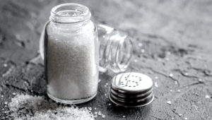salt in glass bottle scattered on dark kitchen table background