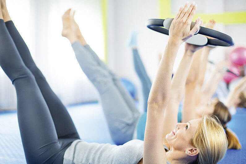 Group of women doing Pilates exercises. Laying side by side on their backs with hand behind heads. They are lifting their legs and strengthening their abdominal muscles. Holding Pilates rings and squeezing them. The closest person to the camera is in focus.