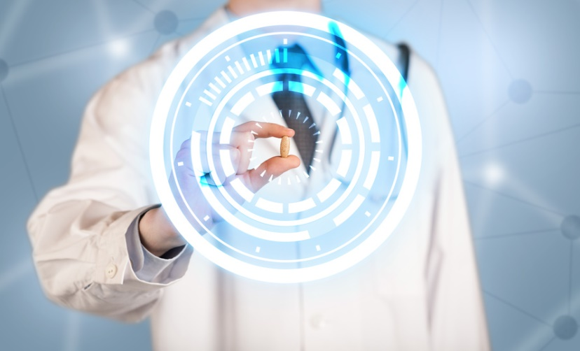 Male doctor holding a pill with glowing circles