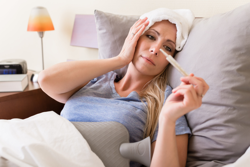 Young sick woman with fever checking her temperature with a thermometer at home