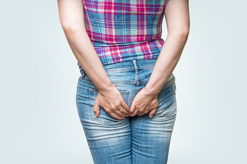 Woman holding her butt isolated on blue background - diarrhea concept