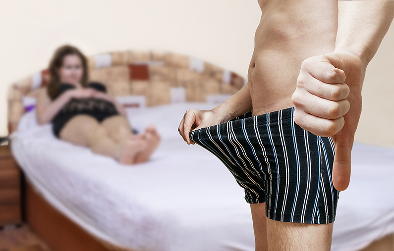 Impotence concept. Woman in bed is waiting on her impotent lover who is looking on his penis and showing thumb down.