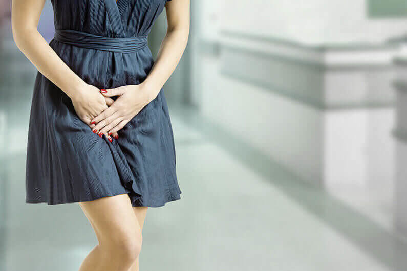 Close up of a woman with hands holding her crotch in an emergency room