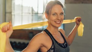 Smiling healthy relaxed athletic young woman standing in an urban gym holding an exercise ribbon over her shoulders as she tones and strengthens her muscles