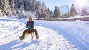 Cheerful girl riding a sled downhill on a snow covered sledge trail in a white sunny winter mountain landscape