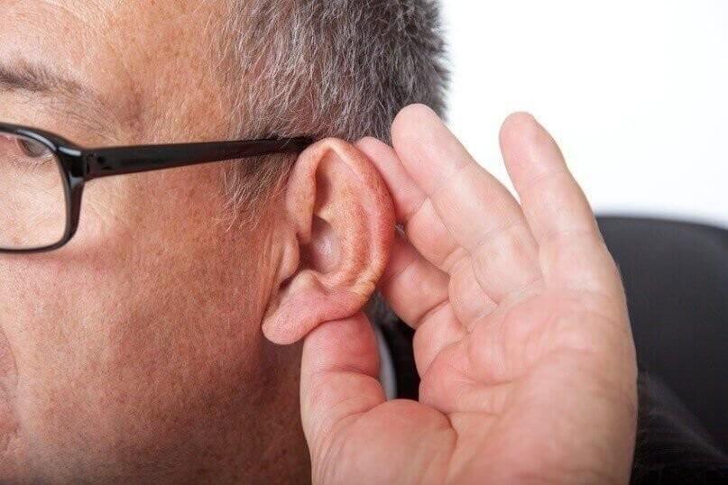 Man holding ear to listen
