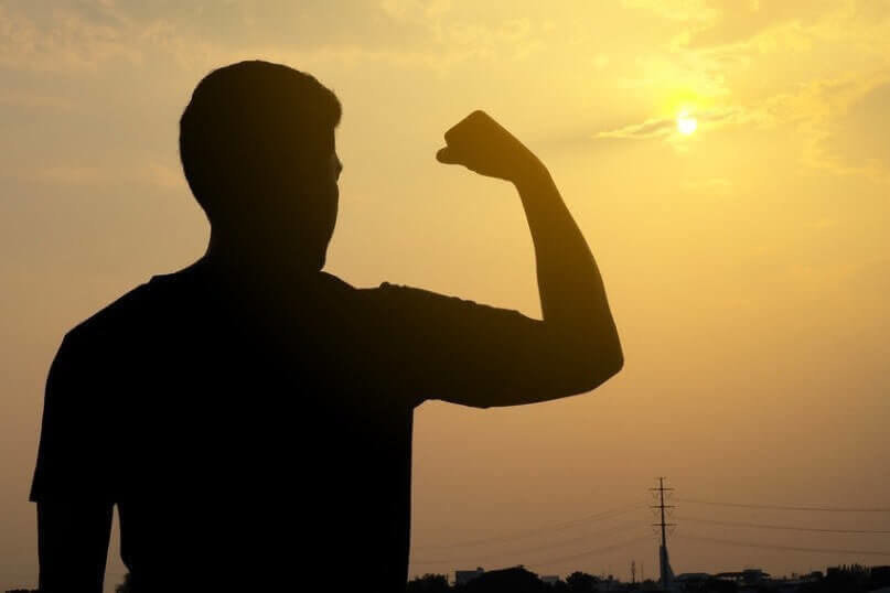 The silhouette of a man, his arms muscles show strong on the background of the sunset.