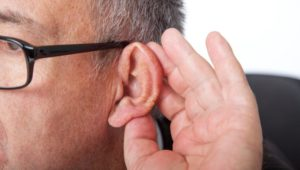 Man holding ear to listen