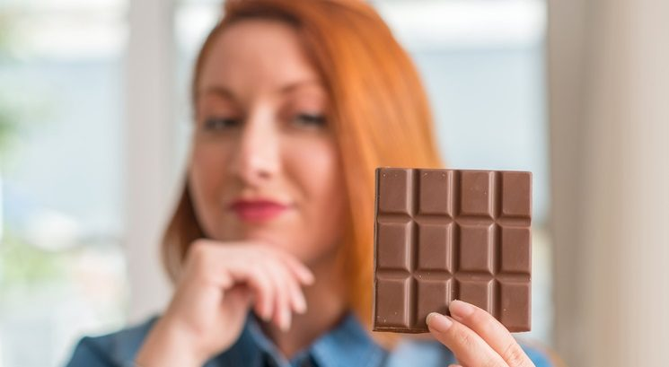 Redhead woman holding chocolate bar at home serious face thinking about question, very confused idea